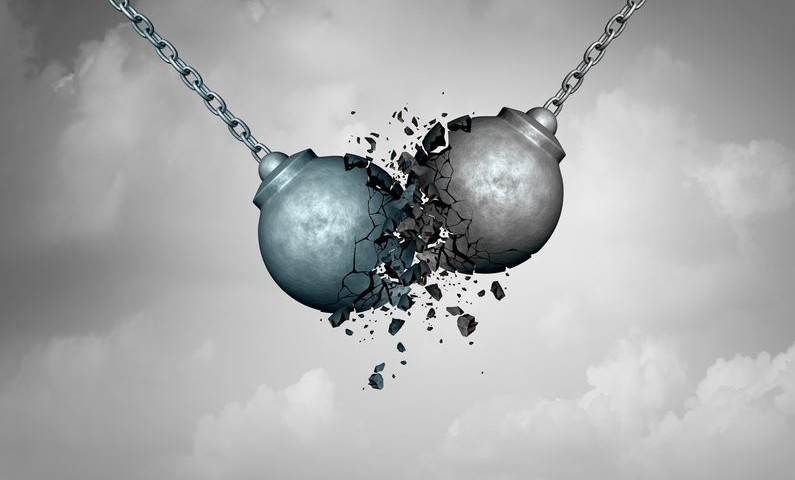 Destructive competition business concept as two wrecking balls colliding together resulting in smashed breakup as a rivalry struggle metaphor as a 3D illustration.