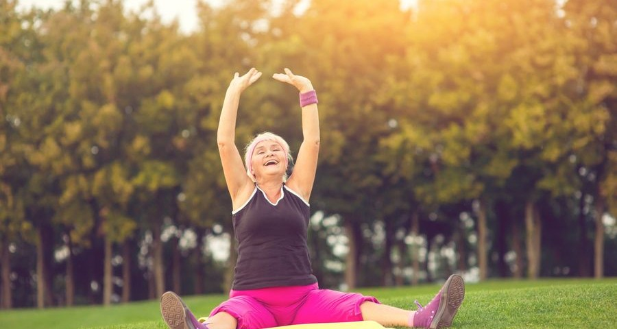 Woman with raised arms sitting. Lady with closed eyes outdoor. Concentrate and breathe deeply. Flexibility and health.