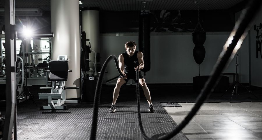 Fitness man working out with battle ropes at gym. Battle ropes fitness man at gym workout exercise fitted body. Fitness man training with battle rope in fitness club.