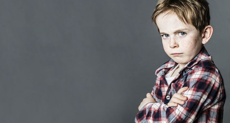 upset little child with freckles standing from profile with arms crossed, pouting and sulking to express his attitude or opposition, contrast effects, long banner