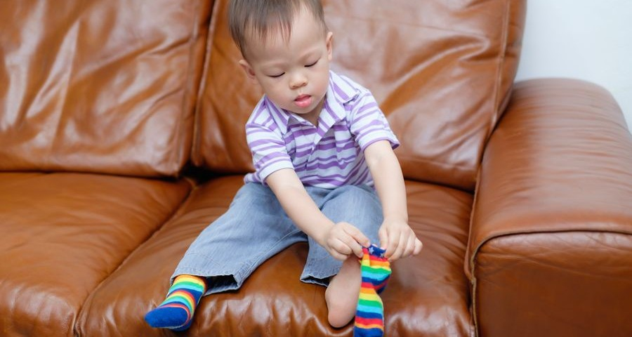 Cute little Asian 18 months / 1 year old toddler boy child sitting on sofa in living room concentrate on putting on his own socks, Encourage Self-Help Skills in Children, Develop Confidence concept
