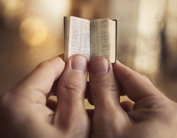 Two hands holding a very small Bible.