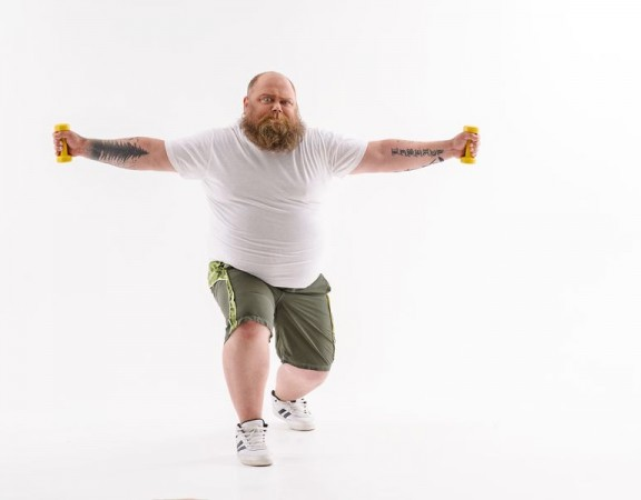 Fat man is lifting dumbbells with efforts. He is standing and stretching arms sideways. Isolated